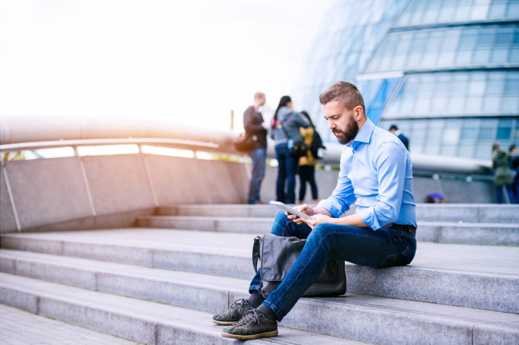 manager-with-tablet-sitting-on-stairs-london-city-PGB92TN